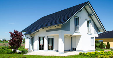 Weißes Einfamilienhaus mit Garten